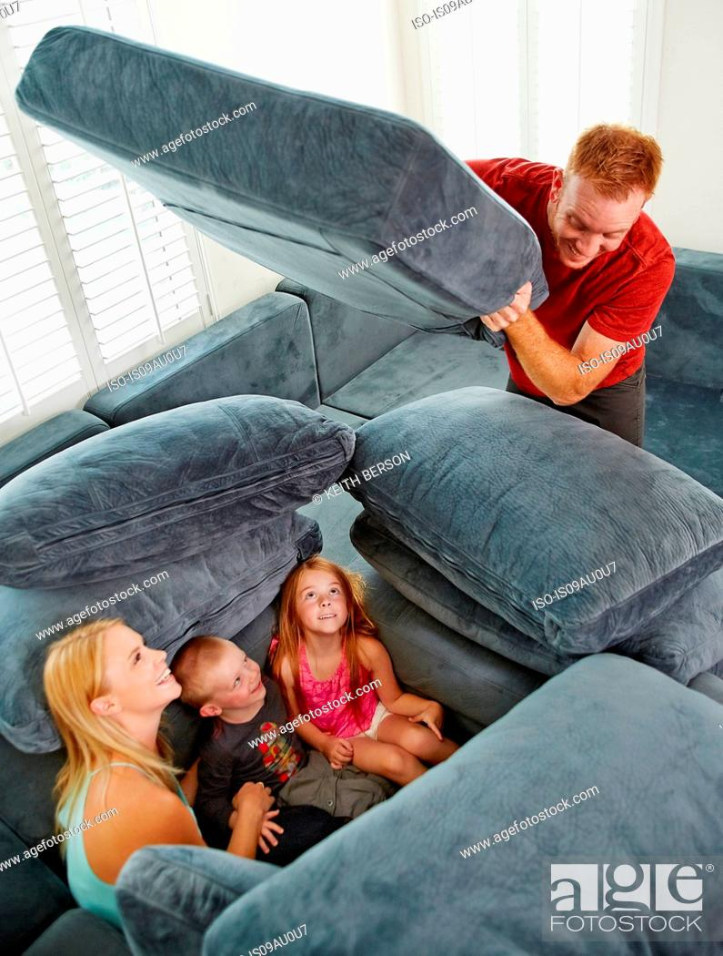 Stock Photo: Father covering family sitting among cushions in living room.