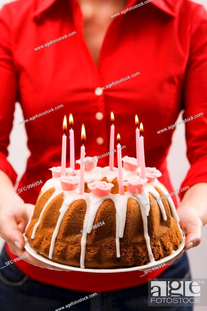 Woman Holding Iced Ring Cake With Birthday Candles Stock Photo