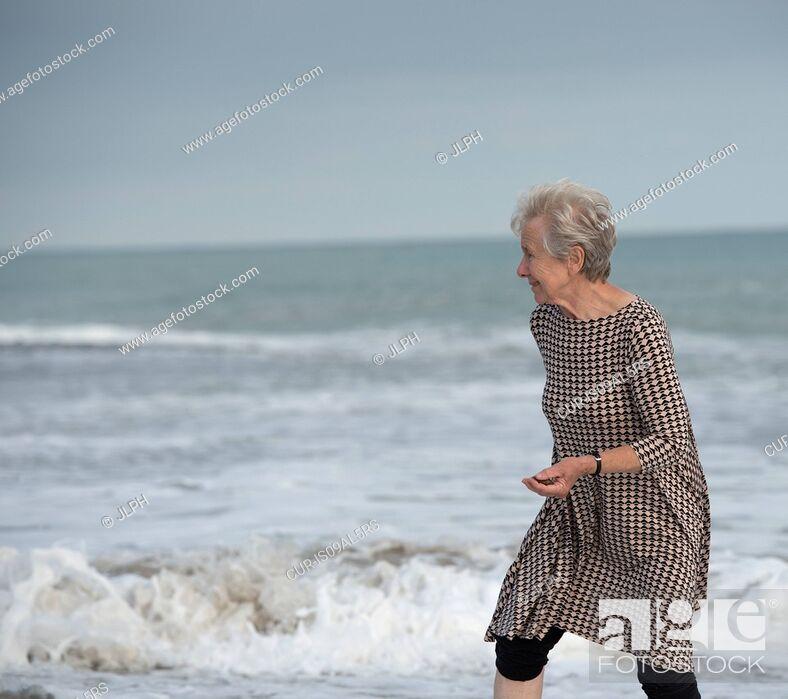 Imagen: Senior woman running from ocean wave on beach, Dana Point, California, USA.