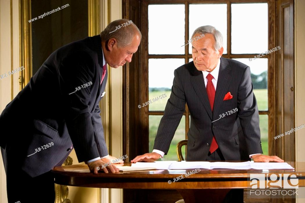 Stock Photo: Businessman at desk showing paperwork to colleague.