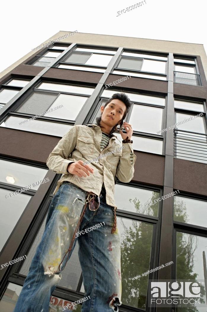 Stock Photo: One young man using mobile phone, low angle view.