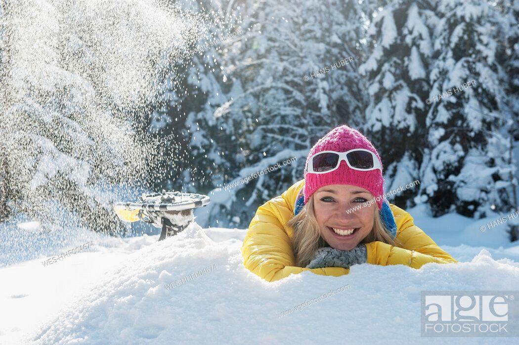 Stock Photo: Austria, Salzburg State, Altenmarkt-Zauchensee, Smiling young woman lying in snow, portrait.