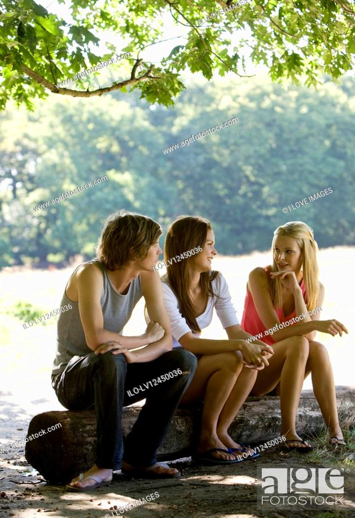 Stock Photo: Three people sitting on a log, talking.