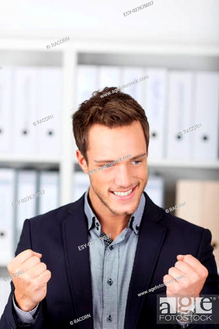 Stock Photo: Successful young businessman clenching fists at the office.