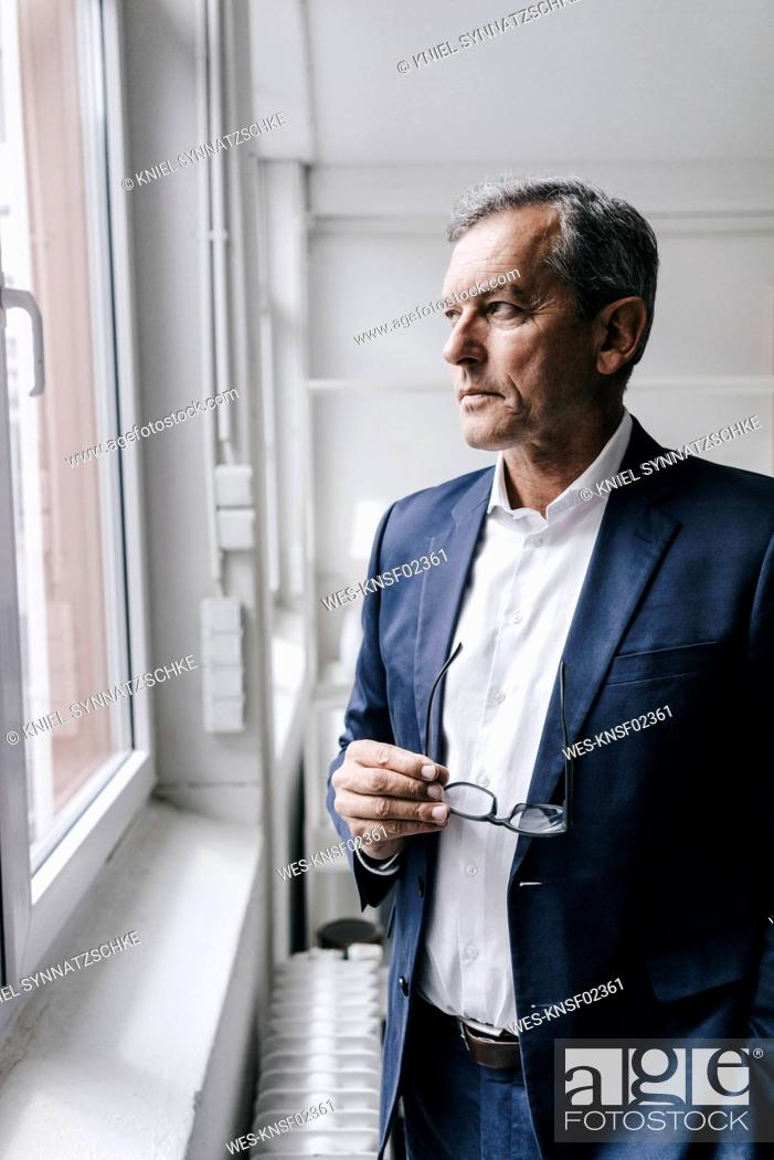 Stock Photo: Serious mature businessman looking out of window.