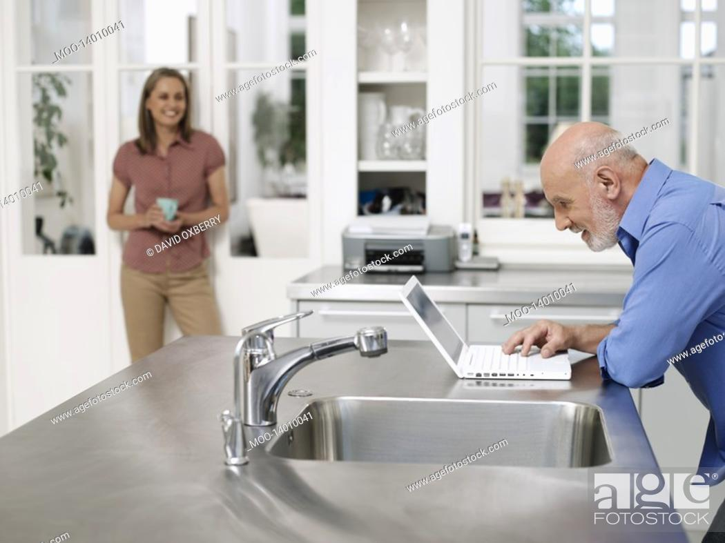 Stock Photo: Man using laptop by kitchen sink woman watching from distance.