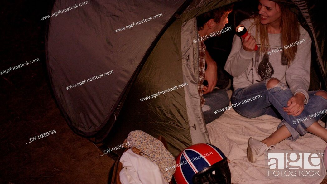 Stock Photo: Young couple with flashlight inside camping tent.