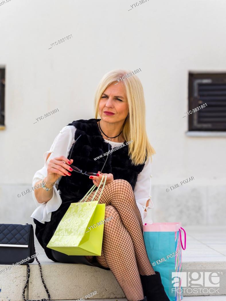 Stock Photo: Attractive shopper woman with her shopping bags is expecting someone.