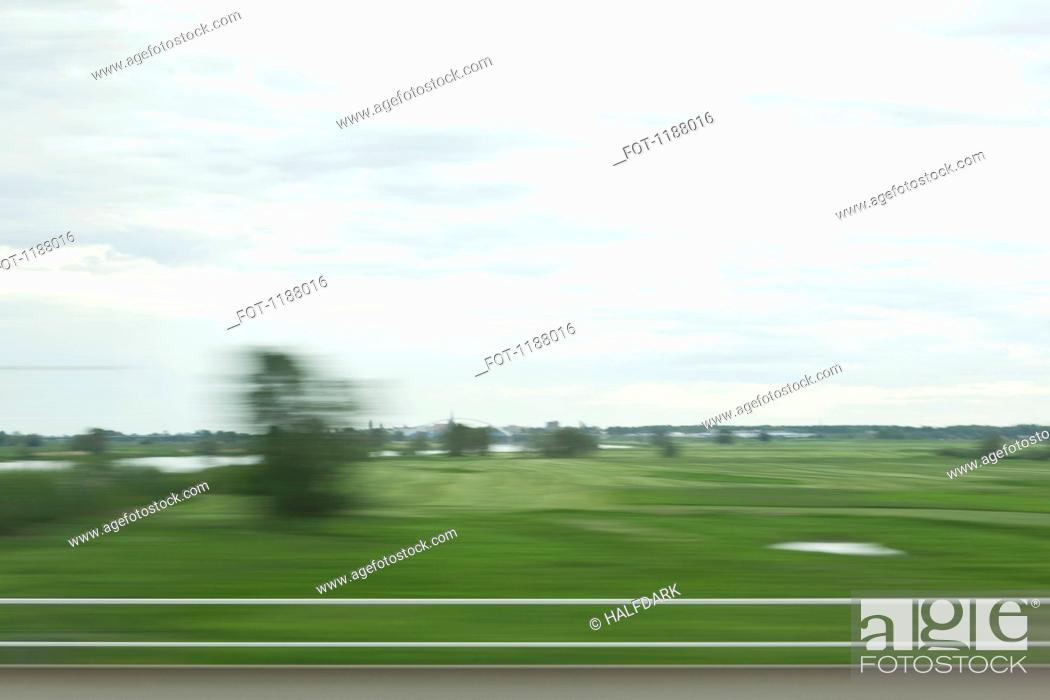Stock Photo: A rural landscape in blurred motion viewed from a moving train.