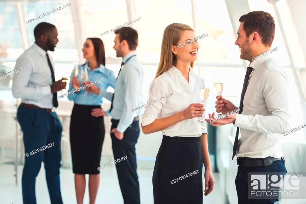 Stock Photo: Successful business people are drinking champagne, talking and smiling while celebrating in office.