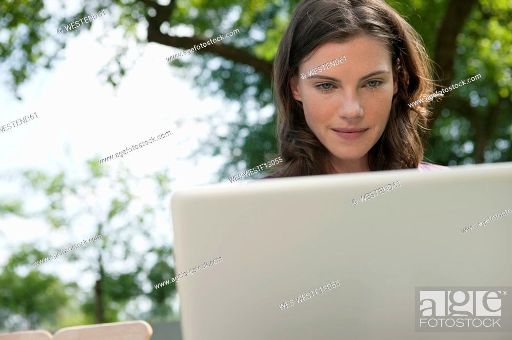 Stock Photo: Germany, Hamburg, Woman using laptop in garden.
