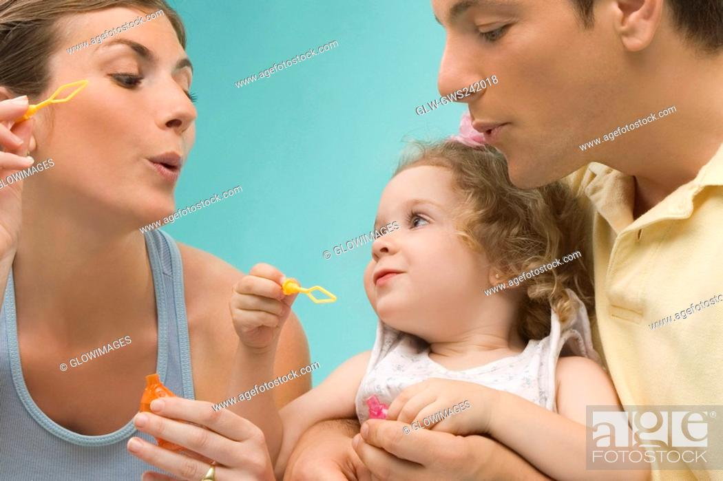 Stock Photo: Close-up of a mid adult couple looking at their daughter.