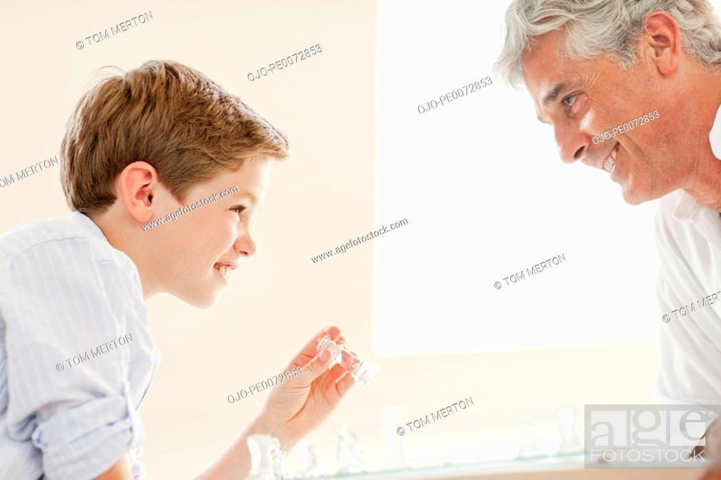 Stock Photo: Father and son playing chess.