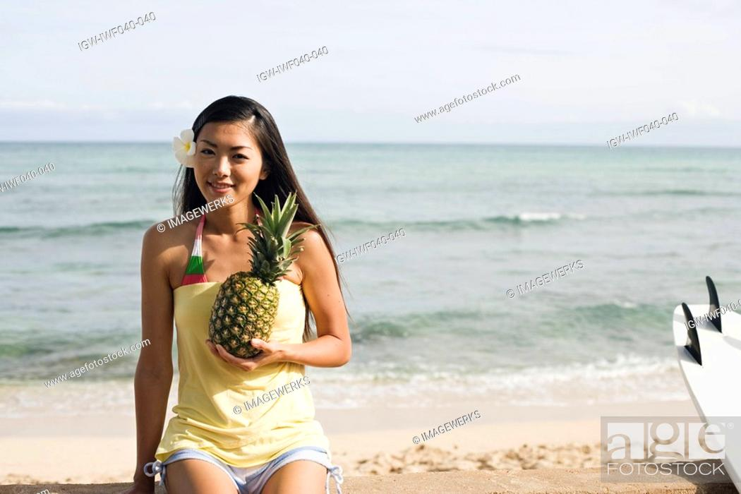 Stock Photo: Portrait of a young woman holding pineapple.