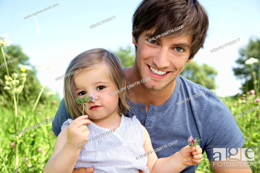 Stock Photo: Germany, Cologne, Father and daughter smiling, portrait.