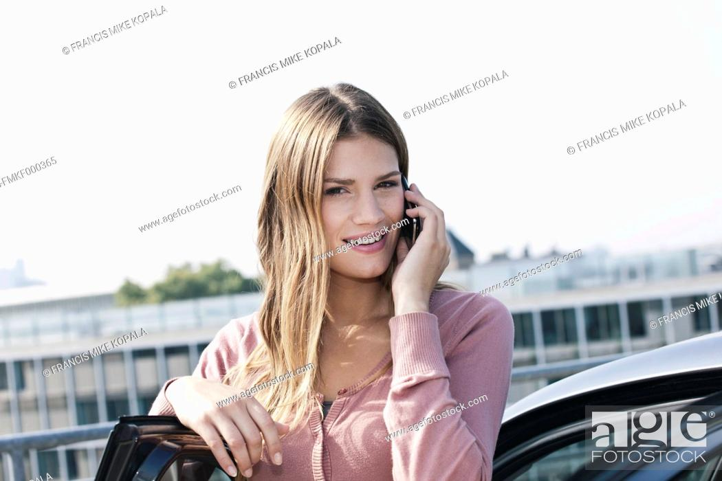 Stock Photo: Germany, Cologne, Young woman on phone near parking lot, smiling, portrait.