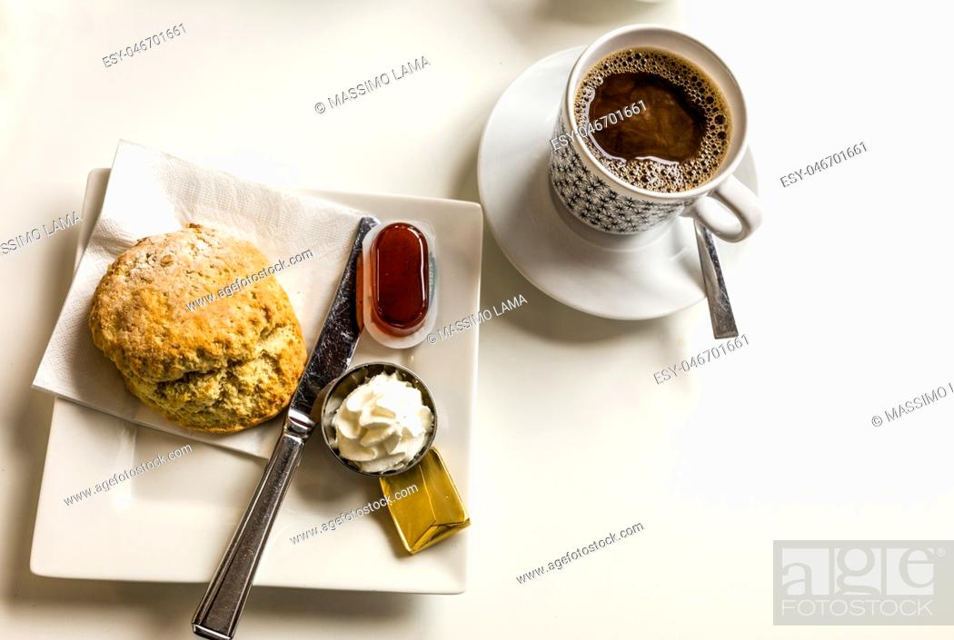 Imagen: coffee and scones with clotted cream and jam, strawberries.