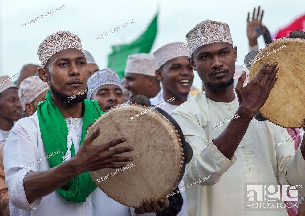 Stock Photo: Sunni muslim men playing tambourines during the Maulidi festivities in the street, Lamu County, Lamu Town, Kenya.