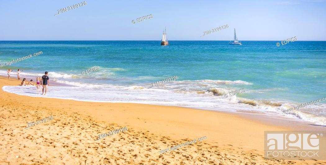 Stock Photo: families at benagil beach with coast tour masted vessel in background, benagil, algarve, portugal.