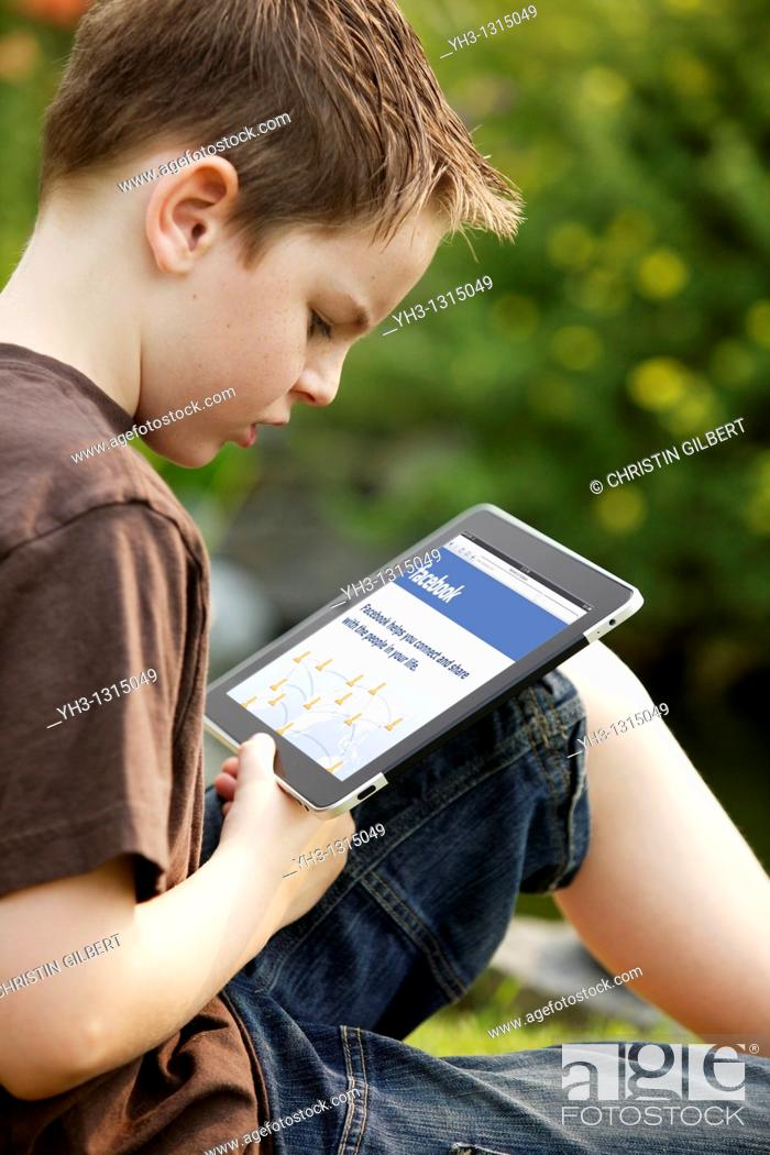 Stock Photo: Young boy using an iPad to check his Facebook account.