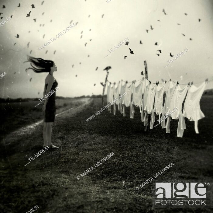Imagen: Conceptual image of a young woman standing alone in fields looking at washing hanging on a line with birds flying.