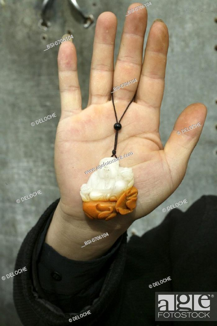 RELIGION<BR>Miniature Buddha, held in palm of hand