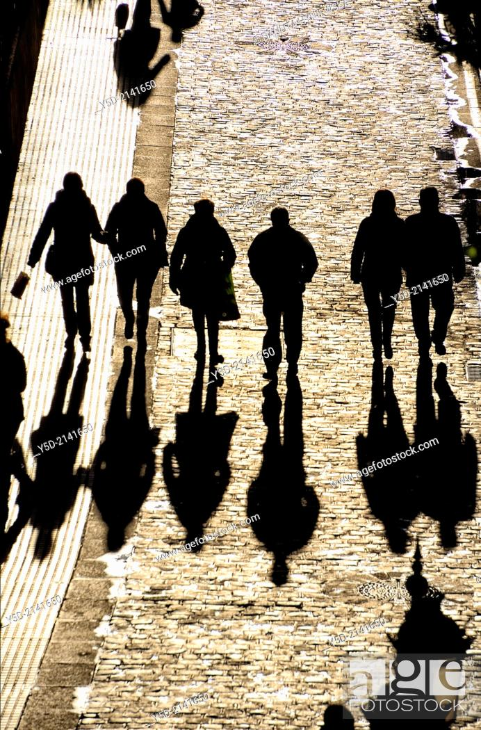 Stock Photo: people walking paved street with long shadows, view from above, Cadiz, Andalusia, Spain.