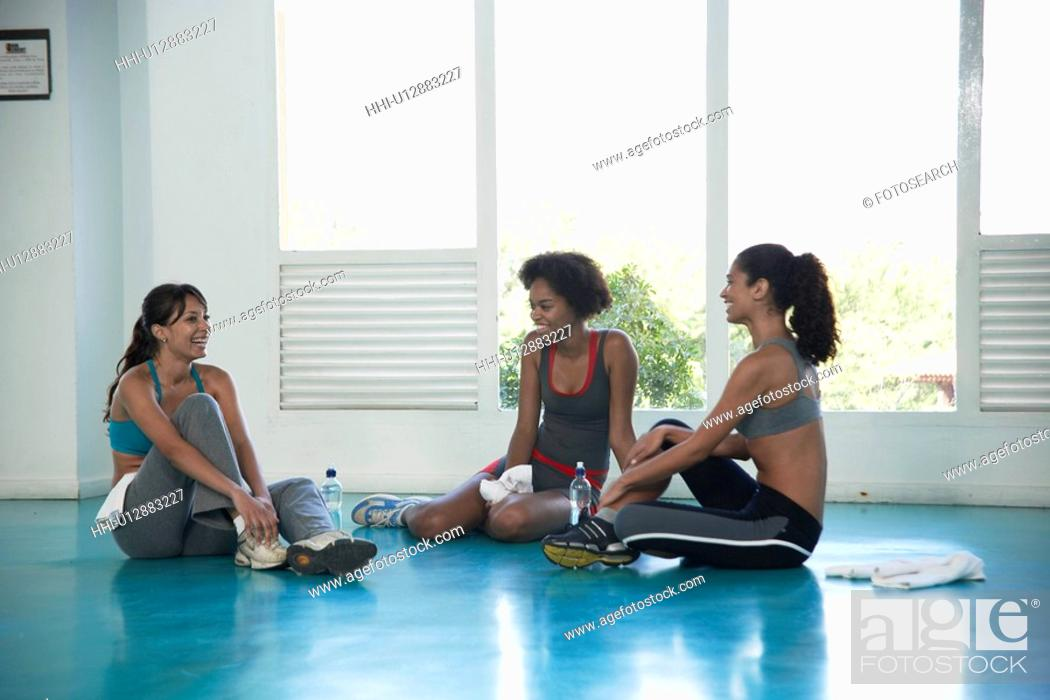 Stock Photo: Women in sports clothing sitting on floor.