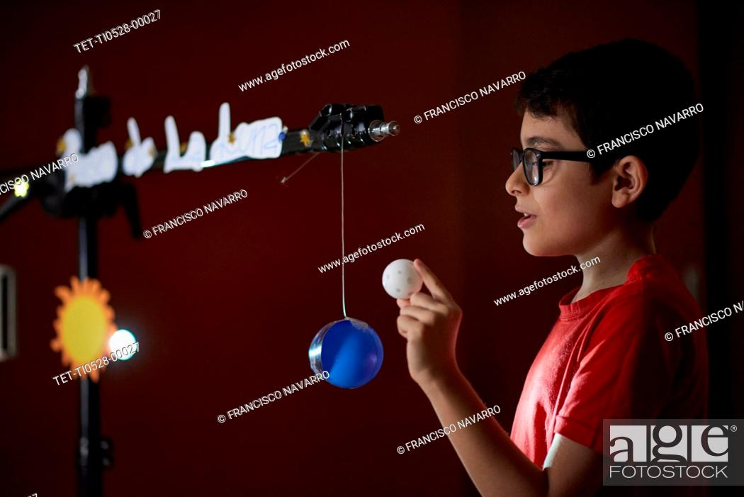Imagen: Boy (8-9) making presentation about sun phases at home school during lockdown.