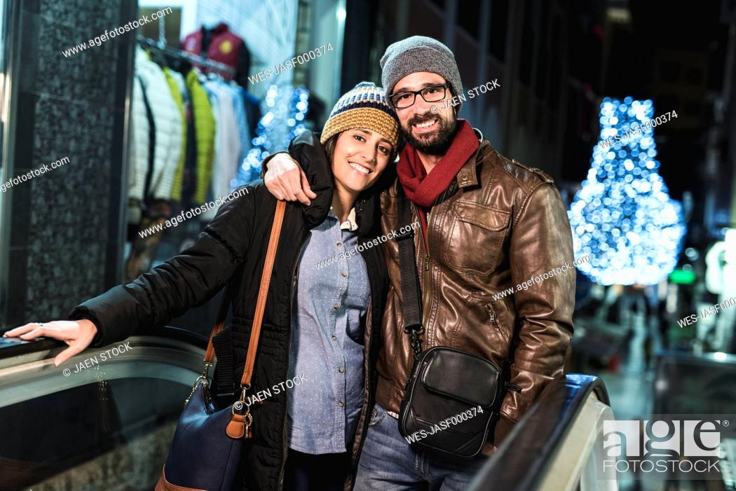 Stock Photo: Couple on escalator with shops and night lights in background.