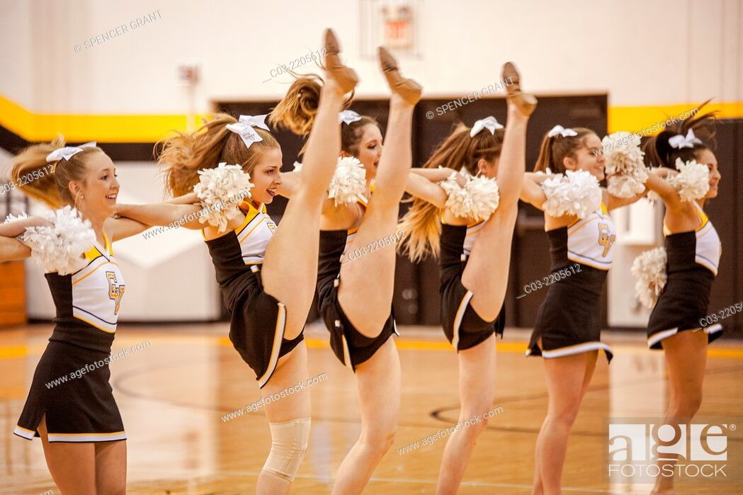 High school cheerleaders perform a high kick during a