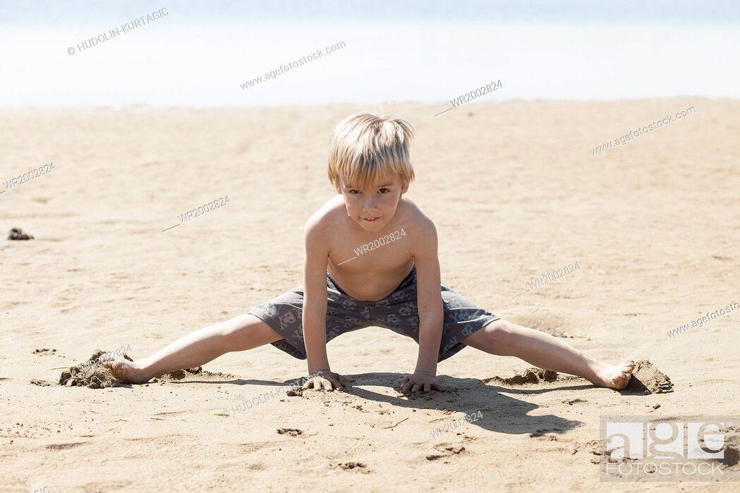 Stock Photo: Blond boy playing on beach.