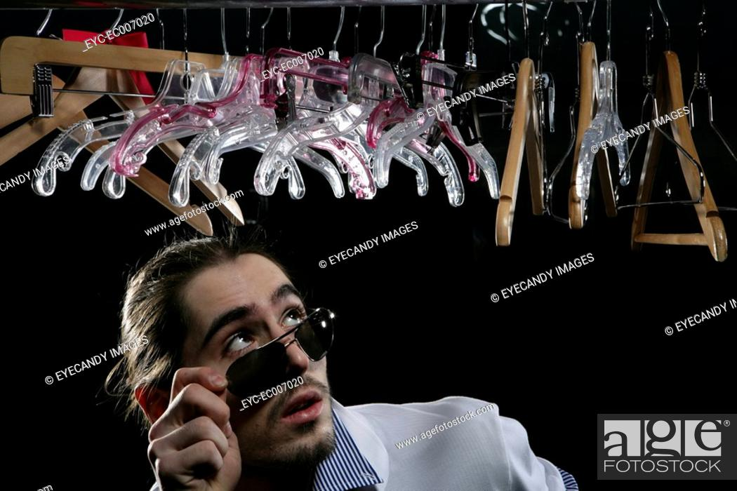 Stock Photo: Young man standing beneath a row of hangers.