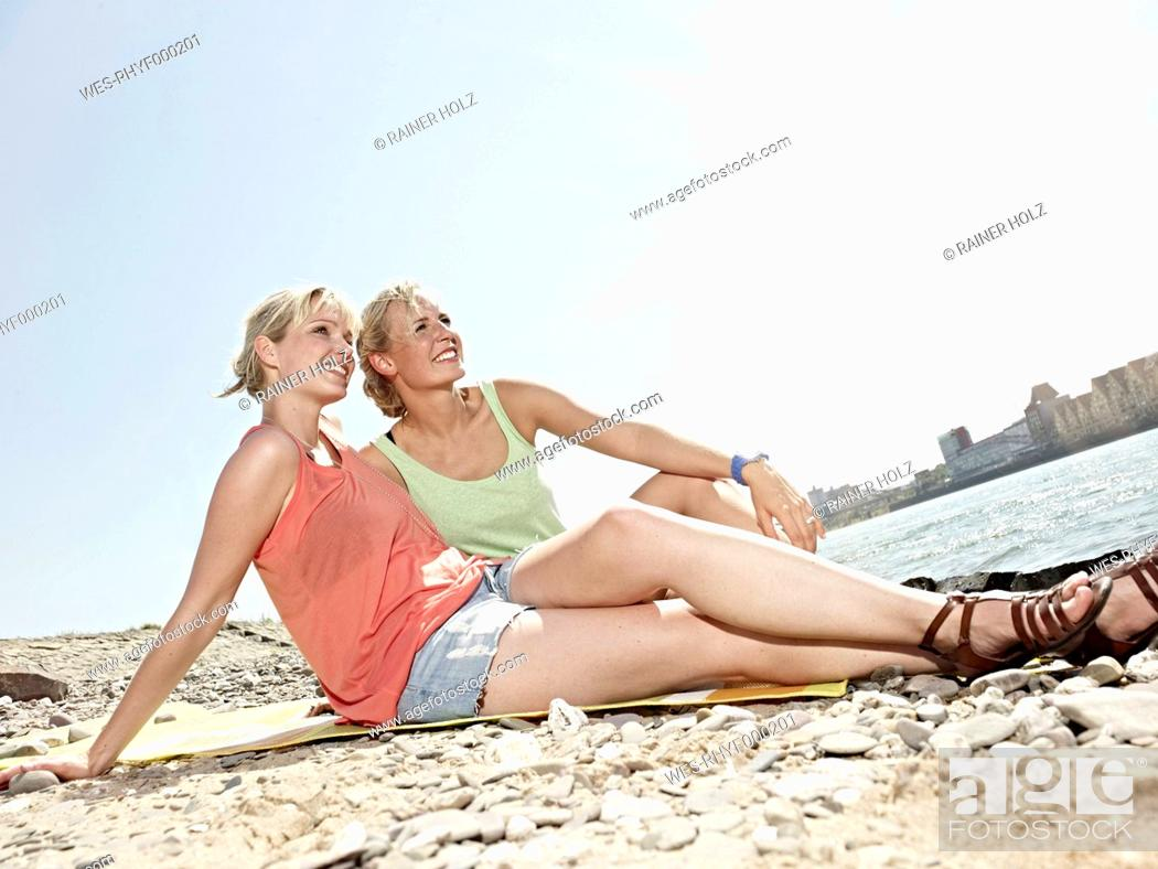 Stock Photo: Germany, Cologne, Young women sitting on riverbank.
