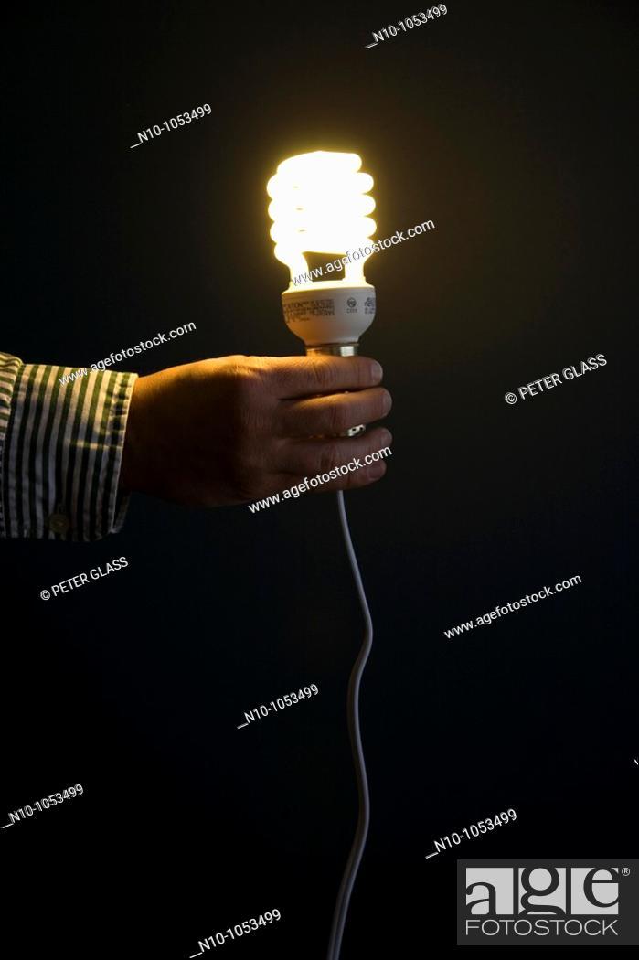 Stock Photo: Close-up of a man holding a fluorescent lightbulb.