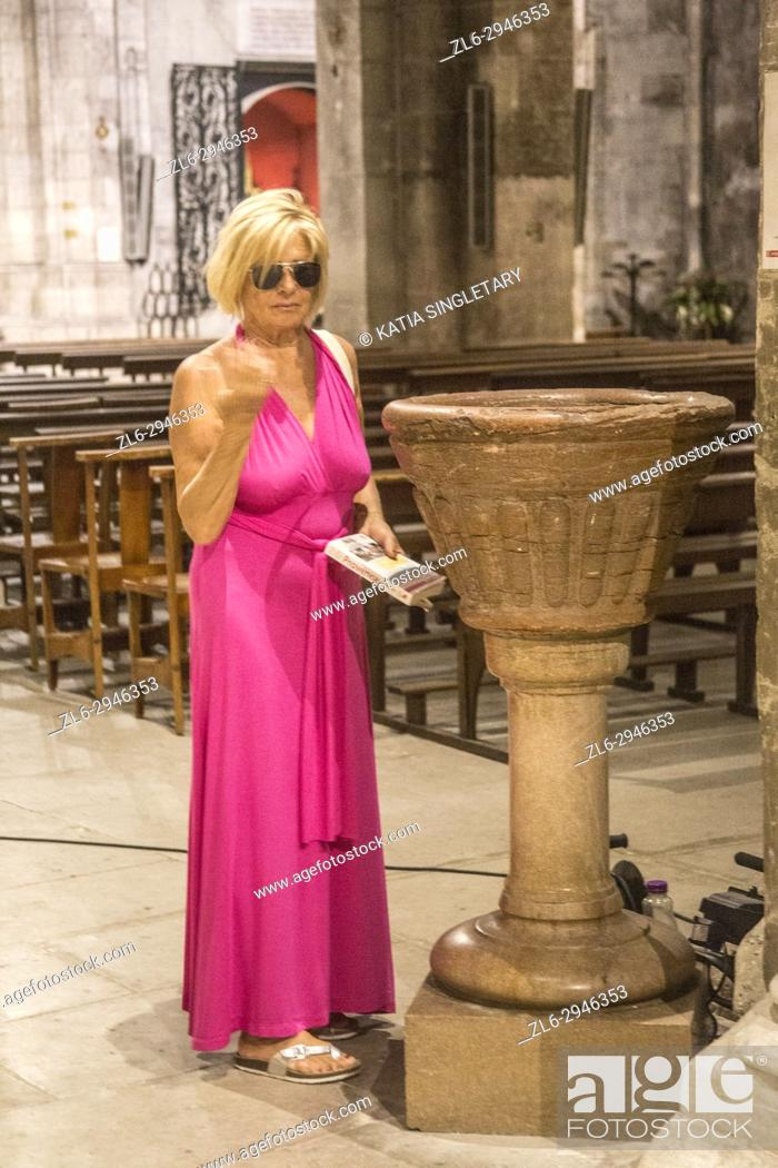Stock Photo: Blond retired senior blond woman with a pink sexy dress and with her sunglasses on. She is dipping her hand in holy water.