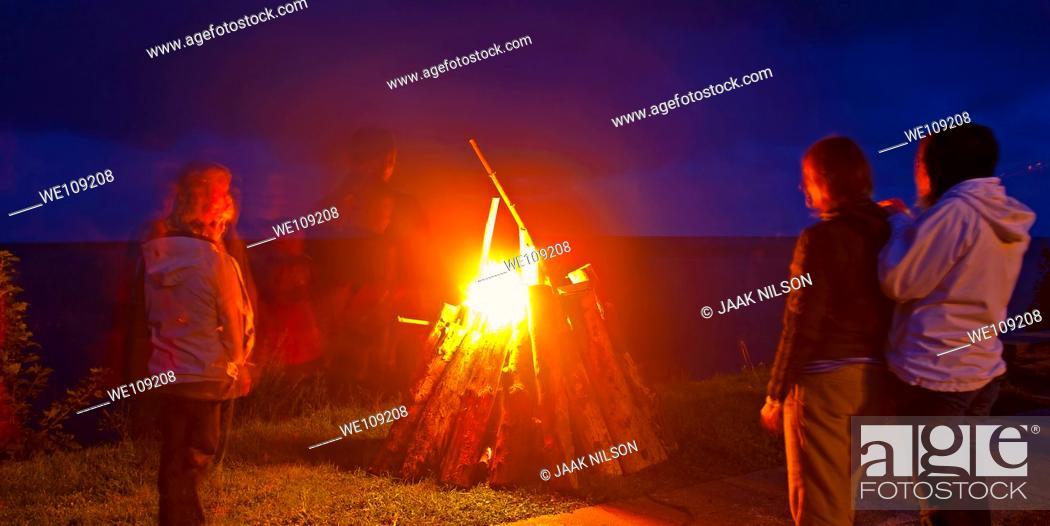 Stock Photo: People standing around bonfire, Estonia.