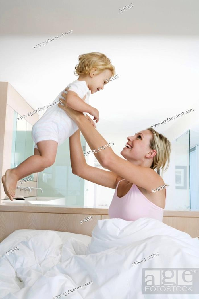 Stock Photo: Young mother holding up baby 12-24 months in bedroom.