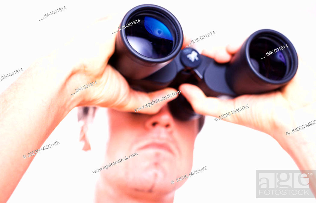 Stock Photo: Portrait of a young man, 20-25 25-30 30-35 years old, looking through binoculars, a spyglass.