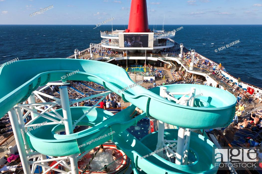 Stock Photo: Cruise passengers on deck and waterslide on Carnival's Triumph cruise ship in the Gulf of Mexico.