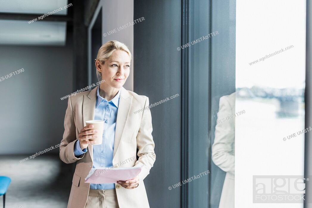 Stock Photo: Businesswoman with coffee and documents at the window.