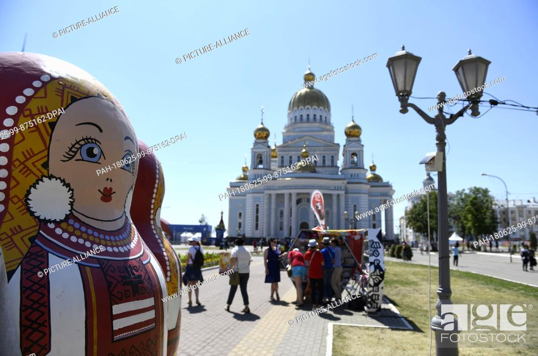Stock Photo: 25 June 2018, Russia, Saransk: Soccer, World Cup: An oversized matryoshka doll before the Russian Orthodox Cathedral of St. Theodore Ushakov.