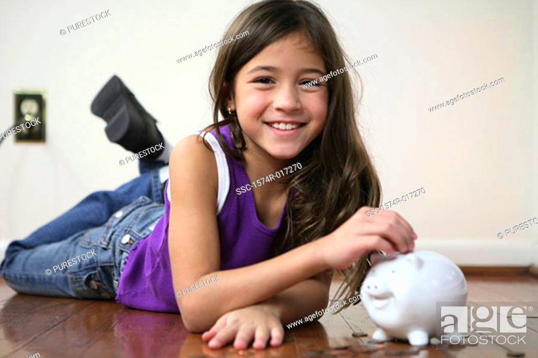 Stock Photo: Portrait of a girl inserting coins into a piggy bank.