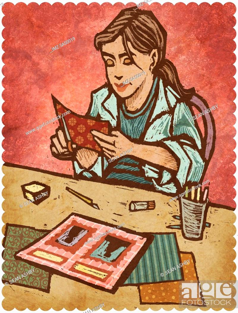 Stock Photo: A woman cutting papers and creating a scrapbook.