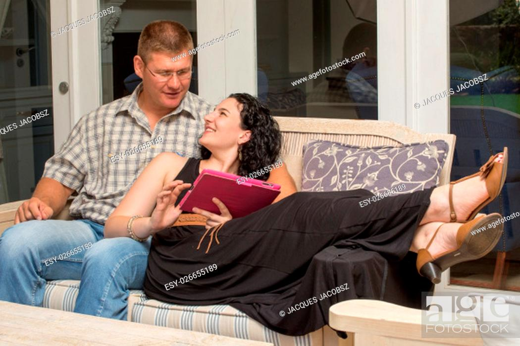 Imagen: A couple sits on a bench with woman lying down with tablet in hand.