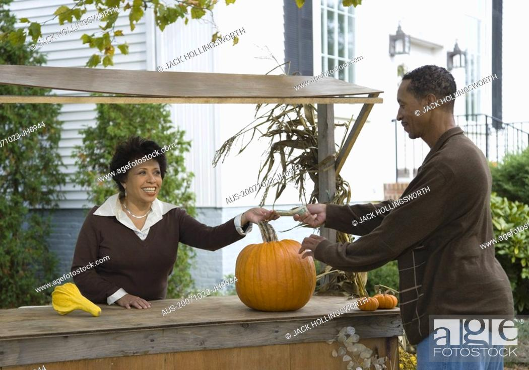 Stock Photo: Side profile of a mature man buying a pumpkin.