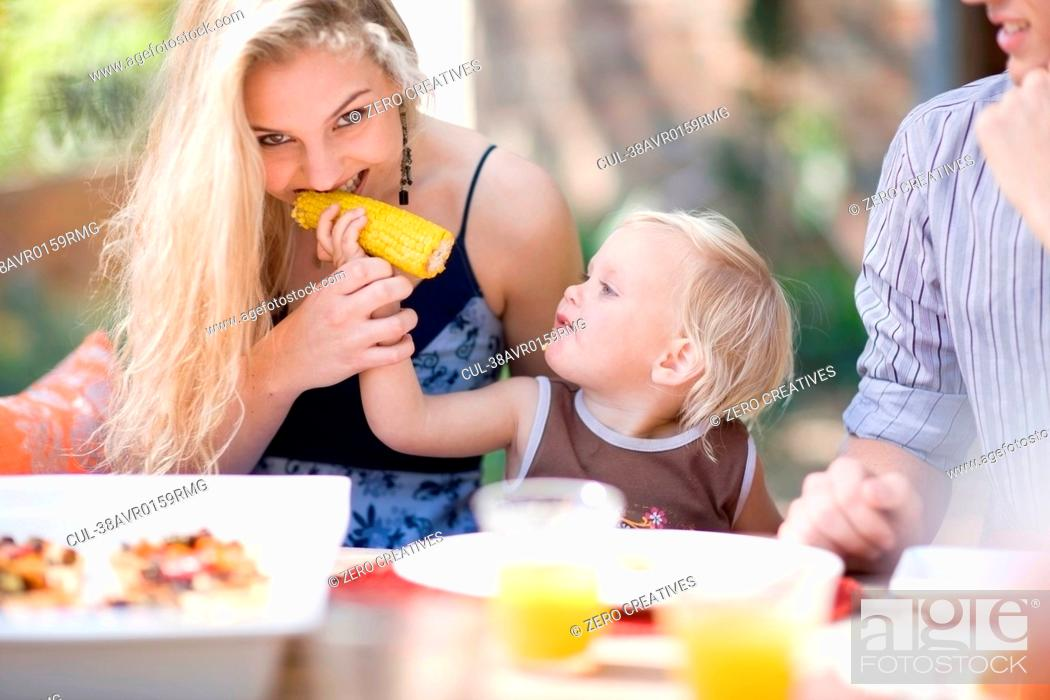 Stock Photo: Toddler feeding mother corn outdoors.