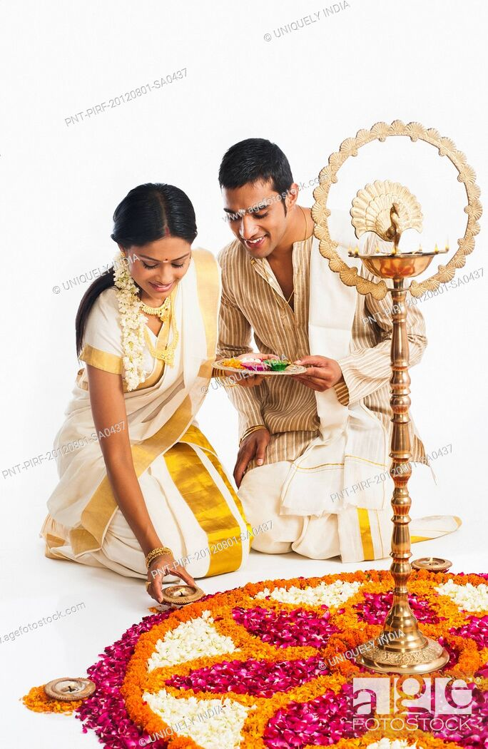 Stock Photo: South Indian couple making a rangoli of flowers at Onam.