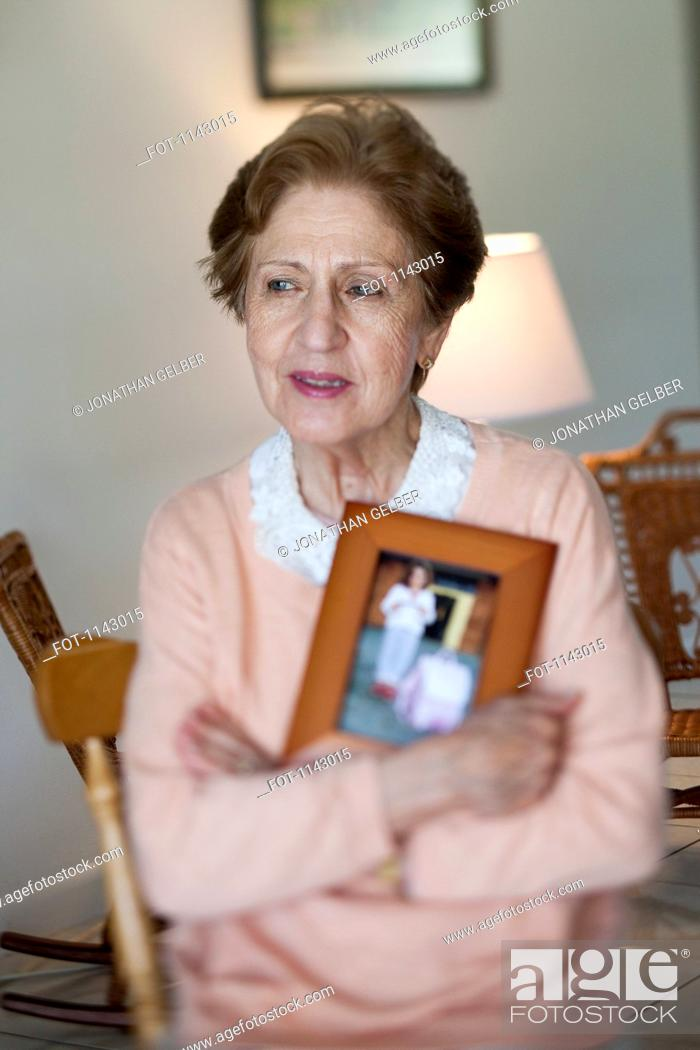 Stock Photo: A senior woman holding a picture frame.