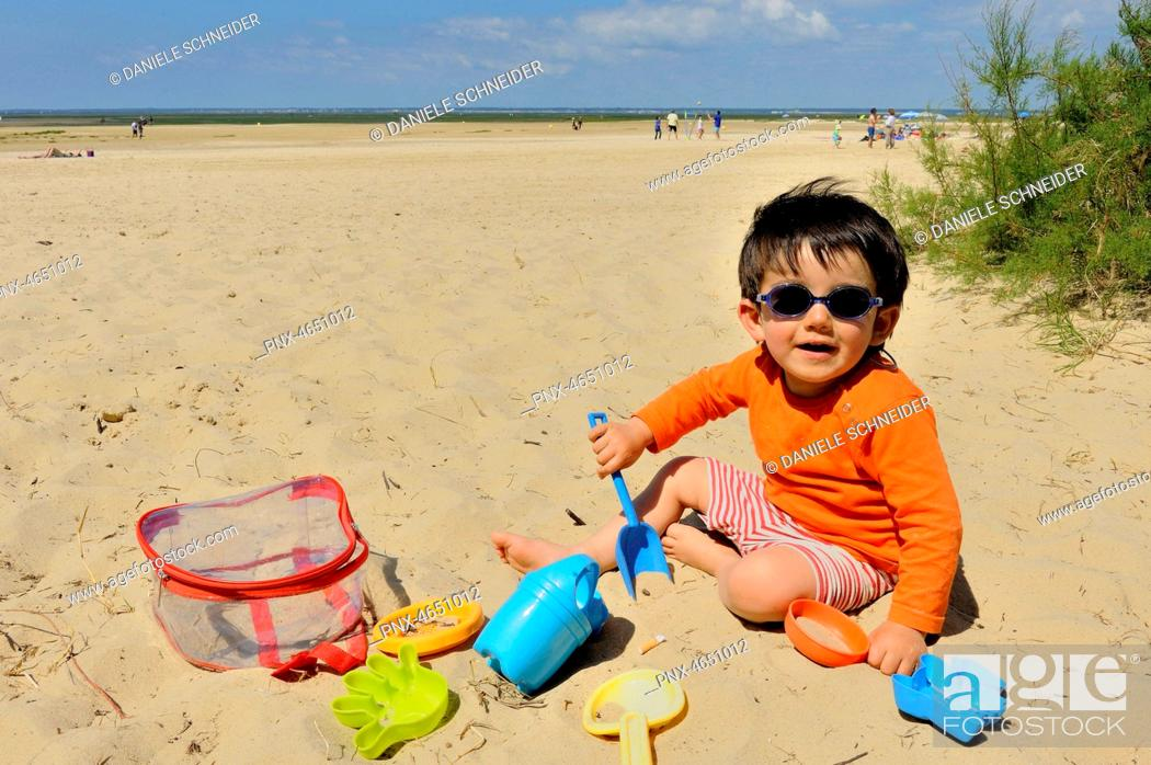 Stock Photo: Two-year-old boy playing with his plastic sand moulds on the beach.